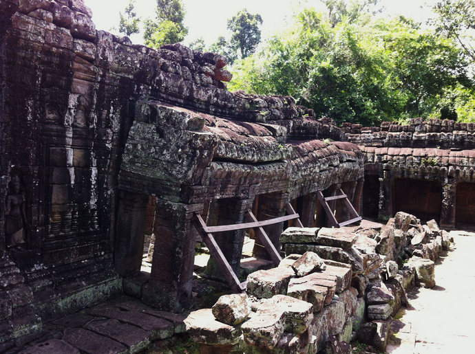 The Side wall of an ancient temple held up by wood to prevent the sculpture from crashing completely